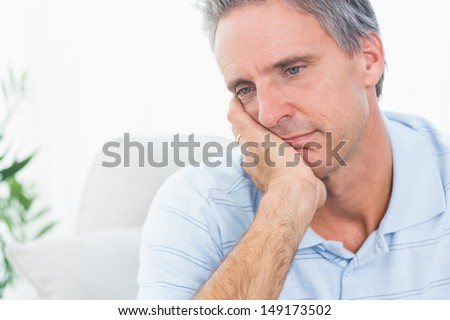Depressed man thinking at home on couch - stock photo