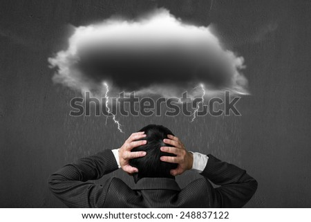 Depressed man with dark cloud rain lightning over his head, concrete wall background - stock photo