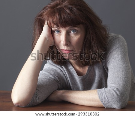 depressed mature woman resting her face on her hands laying down on a table for laziness or frustration - stock photo