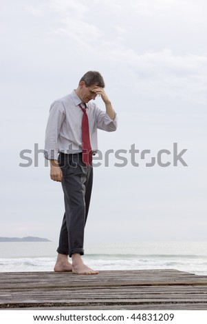 Depressed or worried businessman standing barefoot at the sea - stock photo