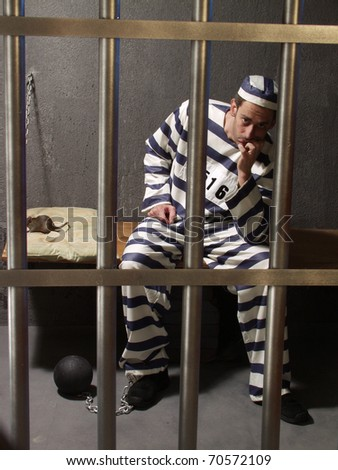 Depressed prisoner in a prison cell. - stock photo