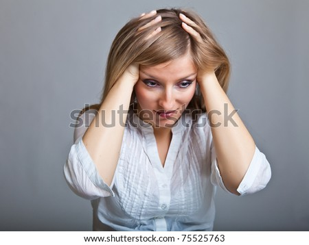Depressed, sad woman on neutral background - stock photo