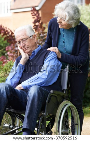 Depressed Senior Man In Wheelchair Being Pushed By Wife - stock photo