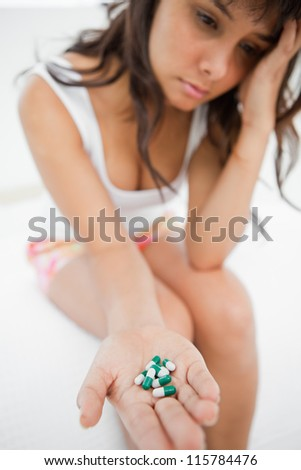 Depressed student holding a lot of medicine while sitting on her bed - stock photo