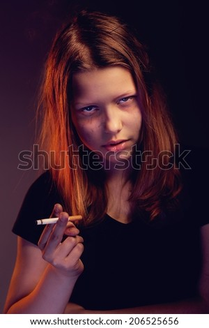 Depressed teen girl with cigarette smoking - stock photo