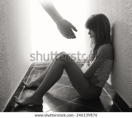 Depressed teenager sitting on the floor while hand coming out from bright background offers support in sepia tones. - stock photo
