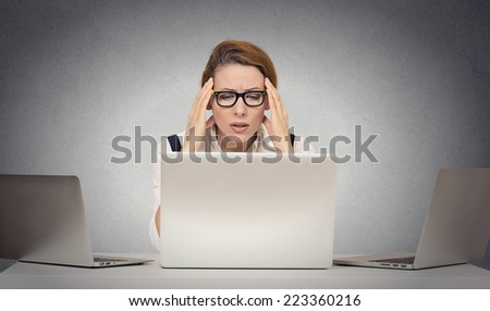 Depressed tired unhappy business woman siting at desk in front of many laptop looking gloomy isolated office grey wall background with copy space. Human face expression emotion feeling life perception - stock photo