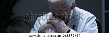 Depressed troubled doctor in his office - panorama - stock photo