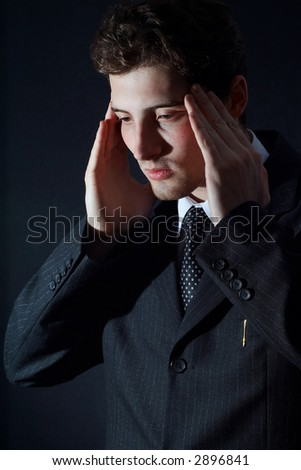 Depressed white collar worker over black background
