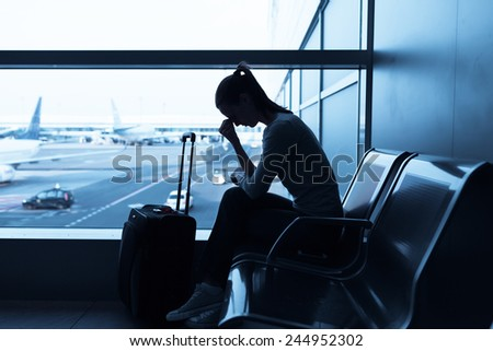 Depressed woman in the airport - stock photo