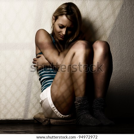 Depressed woman sitting on the floor. - stock photo