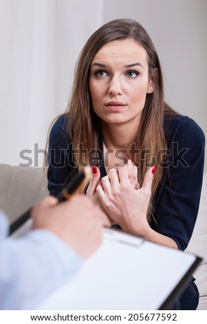 Depressed woman sitting on therapy in cabinet - stock photo