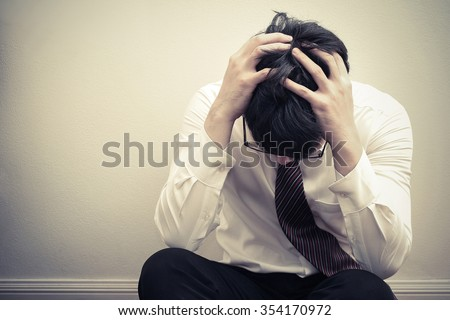 Depressed young asian business man holding his head in hand sitting on floor, depression, unemployed, dismiss - stock photo