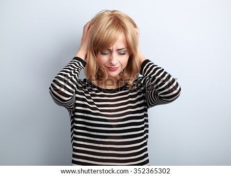 Depressed young blond woman with headache holding head the hands with unhappy face on blue background - stock photo