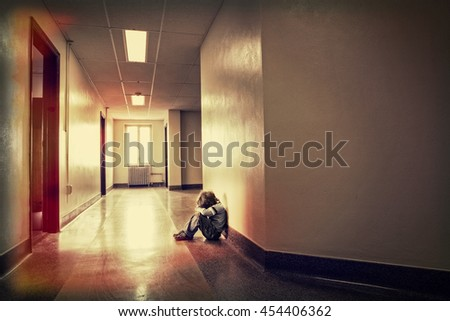 Depressed young boy sitting alone in a hallway