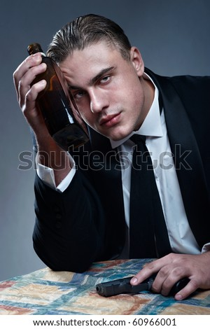 Depressed young man with bottle and black gun in hand - stock photo