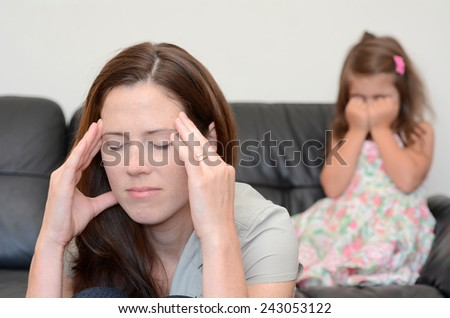Depressed young mother (age 30) with her crying daughter in background.