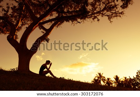Depressed young woman sitting under the tree  - stock photo