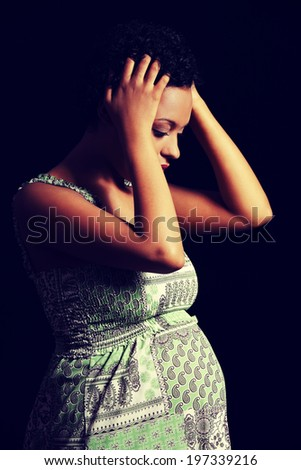 Depression and stress of young pregnant woman against black background