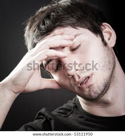 Depression concept - sad young man over black - stock photo