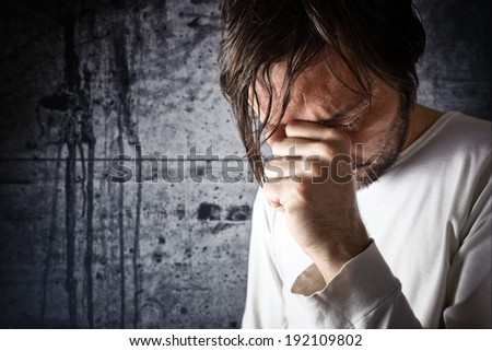 Depressive man crying with hand covering his face, looking upset and showing remorse - stock photo