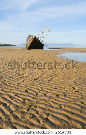 Derelict fishing boat abandoned on a sandy beach - stock photo