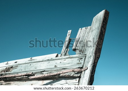 Derelict old wooden boat bow against blue sky, cold toned image effect. Old oyster boat at Bluff, New Zealand. - stock photo