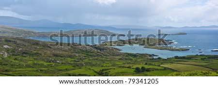 Derrynane Bay, Kerry, Ireland. Panoramic view of rocky islands in a blue sea and distant mountains visible through rain showers, and a rugged pasture of green fields and stone walls in the foreground. - stock photo