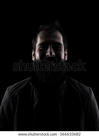 Desaturated laughing man looking at camera. Low key dark shadow portrait isolated over black background. - stock photo