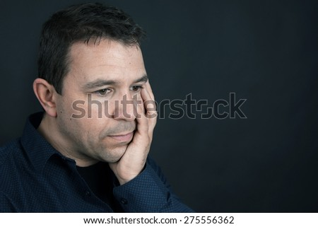 Desaturated portrait of a sad or upset man - stock photo