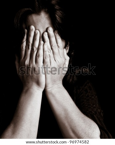 Desaturated portrait of a young woman crying and covering her eyes on a black background with space for text - stock photo
