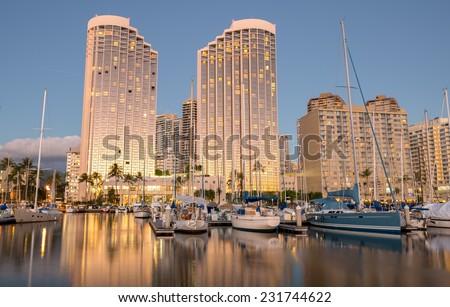 Description:  November 17, 2014, Honolulu, Hawaii:  The setting sun reflects off of the twin towers of the Hawaii Prince Hotel:   November 17, 2014. Title:   Ala Wai Harbor Sunset. - stock photo