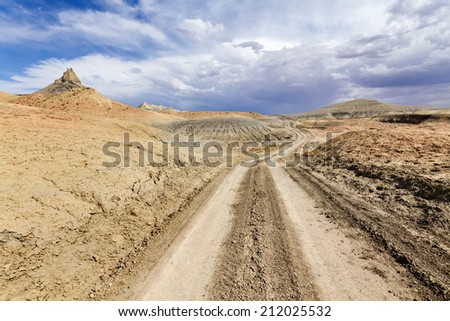 Desert dirt road to Lake Powell under stormy sky, Glen Canyon National Recreation Area. - stock photo