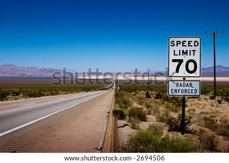 Desert highway to horizon with a speed limit sign on a side. - stock photo