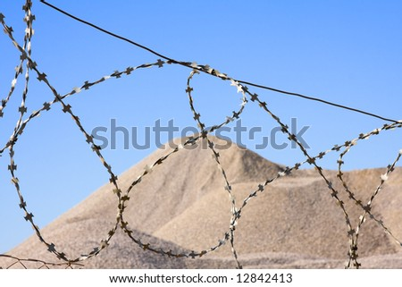 desert hill after barbed wire on blue sky in background - stock photo