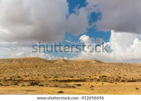 Desert hills under white clouds in blue sky - stock photo