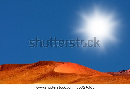Desert landscape shot with red dunes and blue sky with big white sun and yellow grass in the foreground in Namibia - stock photo