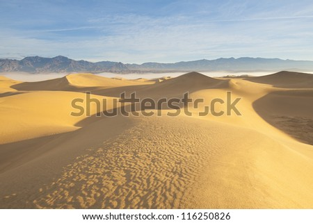 Desert landscape with blue sky and mountain and sand dunes in the foreground - stock photo