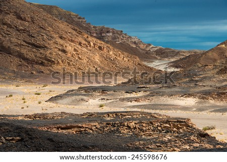 Desert, mountains and cloudy blue sky - stock photo