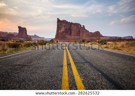 Desert Road at Sunset in Arches National Park taken from middle of Highway - stock photo