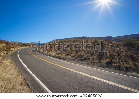 Desert road bends through the wilderness of southern California's Mojave. - stock photo