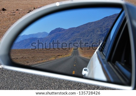 Desert road in Death Valley National Park: rear-view mirror reflection - stock photo