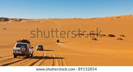 Desert Safari - Off-road vehicles driving in the Sahara Desert, Libya - stock photo