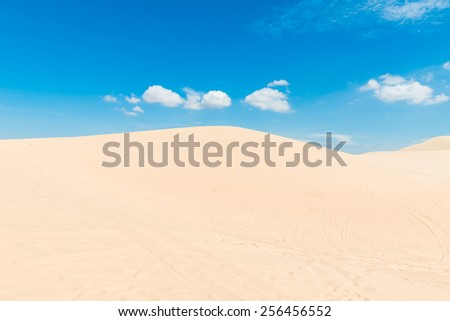 Desert sand dunes landscape with deep blue sky and clouds - stock photo