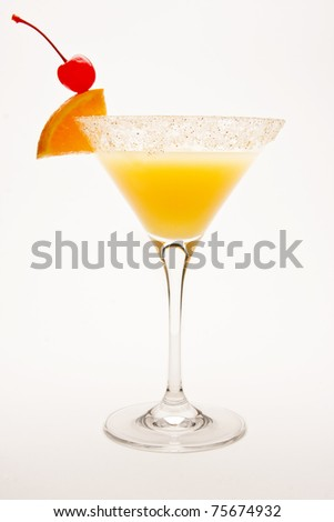 Desert Sand Tequila Sunrise Cocktail against a white background garnished with a cherry and orange wedge. - stock photo