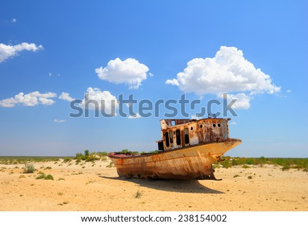 Desert scenic view of a dried Aral Sea with old abandoned boat against the background of bright blue sky around Moynaq, (Muynak or Moynoq), Uzbekistan, Central Asia  - stock photo