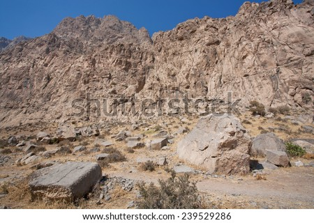 Desert valley with mountain stones and range on a background in the Middle East  - stock photo