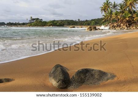Deserted beach and worn stones in Axim, Ghana - stock photo