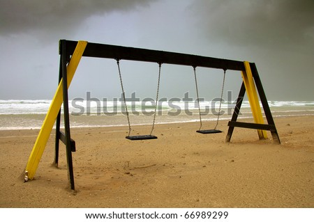 Deserted beach swing on a stormy day - stock photo