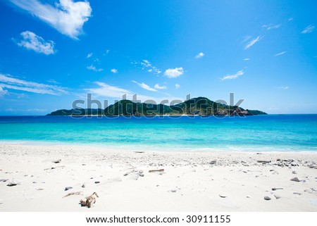Deserted coral island on the horizon - stock photo